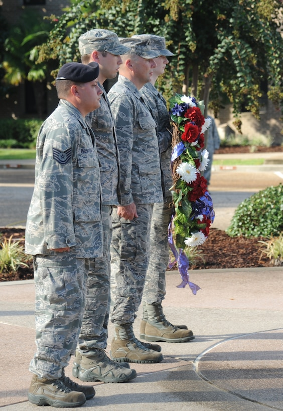 Tech. Sgt. Jason Palmitessa, 81st Security Forces; Staff Sgt. Stephen Jensen, 81st medical Operations Squadron; Brig. Gen. Patrick Higby, 81st Training Wing commander, and Airman 1st Class Codee Potts, Keesler firefighter, prepare to place a wreathe on display during a remembrance ceremony Sept. 11, 2014, Keesler Air Force Base, Miss. The ceremony honored those who lost their lives during the 9/11 attacks.  (U.S. Air Force photo by Kemberly Groue)