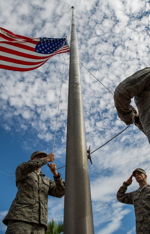 Airmen lower the flag during a 9/11 memorial retreat ceremony Sep. 11, 2014, at Joint Base Charleston, S.C. The retreat ceremony was a poignant reminder of the events of 13 years ago, and the continuing efforts today's military is making against the War on Terrorism. (U.S. Air Force photo/Airman 1st Class Clayton Cupit)