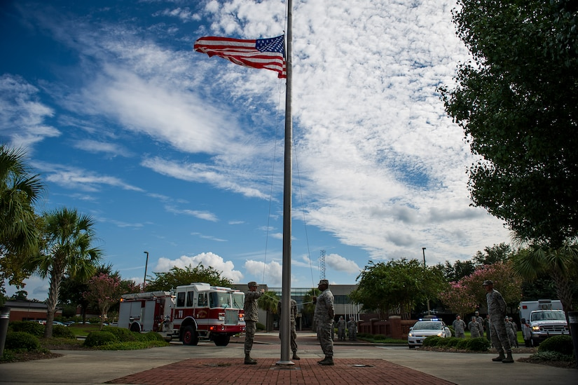Airmen prepare to lower the colors during a 9/11 memorial ceremony Sep. 11, 2014, at Joint Base Charleston, S.C. The flag was flown at half staff through out the nation in memory of the victims of 9/11. The retreat ceremony was a poignant reminder of the events of 13 years ago, and the continuing efforts today's military is making against the War on Terrorism. (U.S. Air Force photo/Airman 1st Class Clayton Cupit)