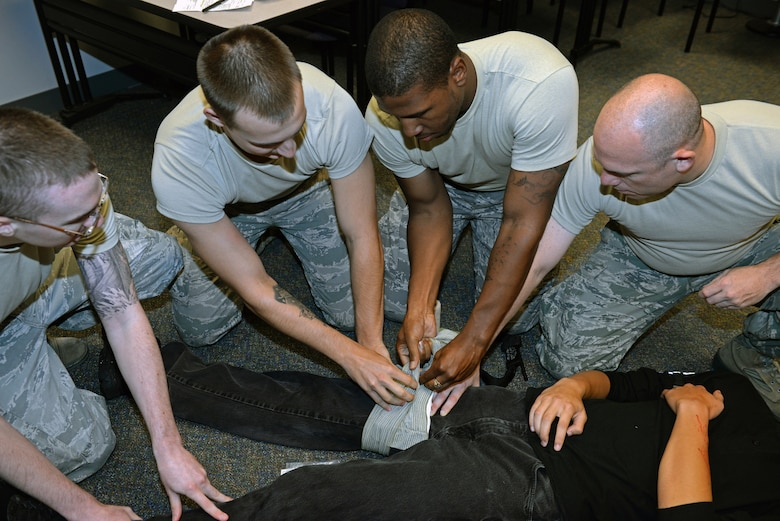 375th Communications Group Airmen put two to three minutes of pressure on a simulated wound of