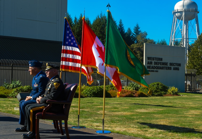 Col. Pete Stavros (left), Western Air Defense Sector commander and Steven Saymon, retired Brooklawn Police Department police inspector, listen to opening remarks Sept. 11, 2014, during the WADS 9/11 memorial ceremony at Joint Base Lewis-McChord, Wash. WADS unveiled a new memorial inside their lobby where three artifacts from the terrorist attacks were displayed. (U.S. Air Force photo/Staff Sgt. Russ Jackson)