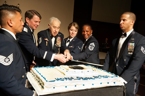 """Retired Master Sgt. James """"Gunner"""" Jackson and Airman Larissa Atkinson, 8th Operations Support Squadron aviation resource manager, as the most senior and junior Airmen, participate in the cake cutting ceremony with Lt. Gen Jan-Marc Jouas, 7th Air Force commander, and Chief Master Sgt. Shelina Fray, 7th Air Force command chief, during the 67th Air Force Ball in Seoul, Republic of Korea, Sept.13, 2014. It is tradition for the oldest and youngest Airmen in attendance to make the ceremonial first cut of the cake. (U.S. Air Force photo by Senior Airman Matthew Lancaster)"""