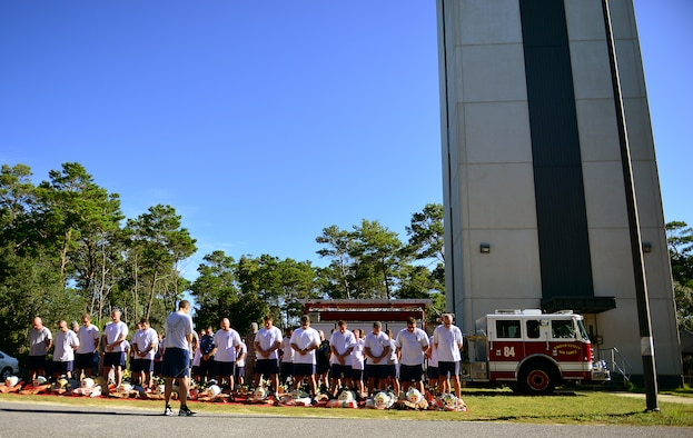 Eglin Air Force Base firefighters participate in a prayer before donning their gear and completing their annual 9/11 memorial tower climb, Sept. 11.  Firefighters carried identification tags of each of the 343 firefighters killed on 9/11 to the top of the air traffic control tower to be placed on a memorial display.  Once at the top the name was read aloud.  The event ended with participants hanging the display over the balcony of the tower with an American Flag. (U.S. Air Force photo/Tech. Sgt. Cheryl L. Foster)