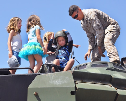 Following a street ride in the Assault Amphibious Vehicle, a Marine assigned to Marine Corps Systems Command's Amphibious Vehicle Test Branch shows girls around the vehicle. Through a community partnership with the YMCA, AVTB sponsored the YMCA Adventure Princess Program Sept. 6 at Camp Pendleton, California. During the event, AVTB provided demonstrations, displays and tours for 37 fathers and 48 daughters from the local community.