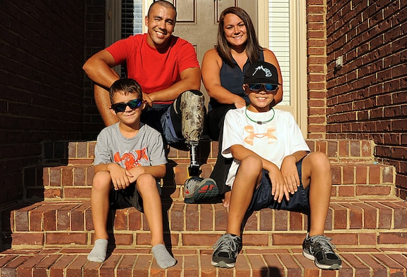 Staff Sgt. Rey Edenfield poses with his wife, Amy, and their two sons, Grayson, left, and Dawson on the front porch of their home Aug. 28, 2014. The picture was taken almost a year after Edenfield was involved in a motorcycle accident that resulted in his left leg being amputated six inches below the knee. Edenfield is an air traffic controller at Maxwell Air Force Base, Ala. (U.S. Air Force photo/Staff Sgt. Erica Picariello)