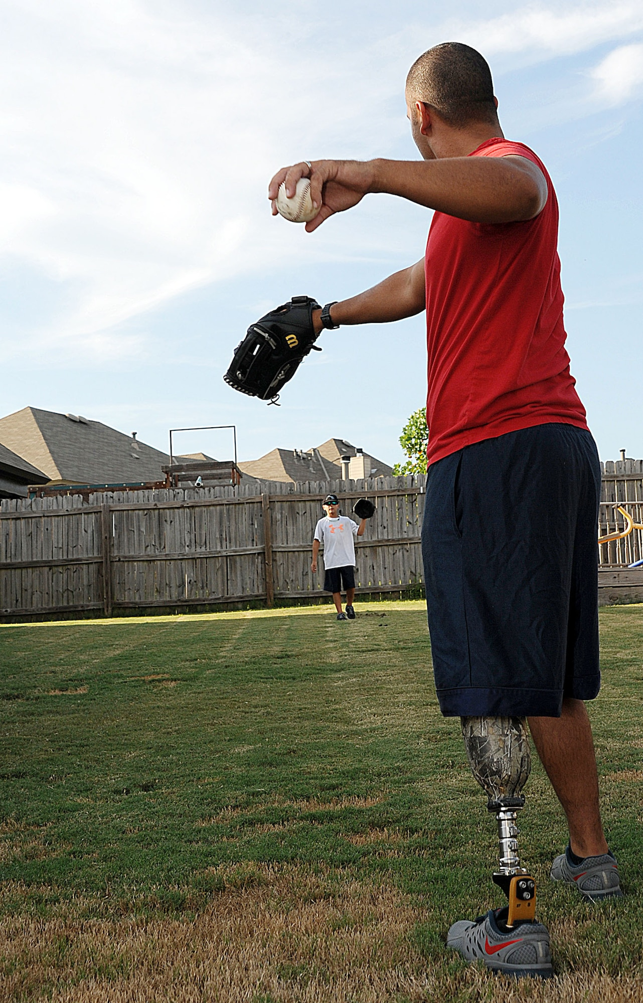 Staff Sgt. Rey Edenfield plays catch with his son, Dawson, Aug. 28, 2014, in the backyard of their family home. Edenfield was involved in a motorcycle accident that resulted in the family decision to amputate his left leg six inches below the knee. Edenfield's prosthetic allows him to maintain his mobility and stay on active duty as an air traffic controller at Maxwell Air Force Base, Ala. (U.S. Air Force photo/Staff Sgt. Erica Picariello)
