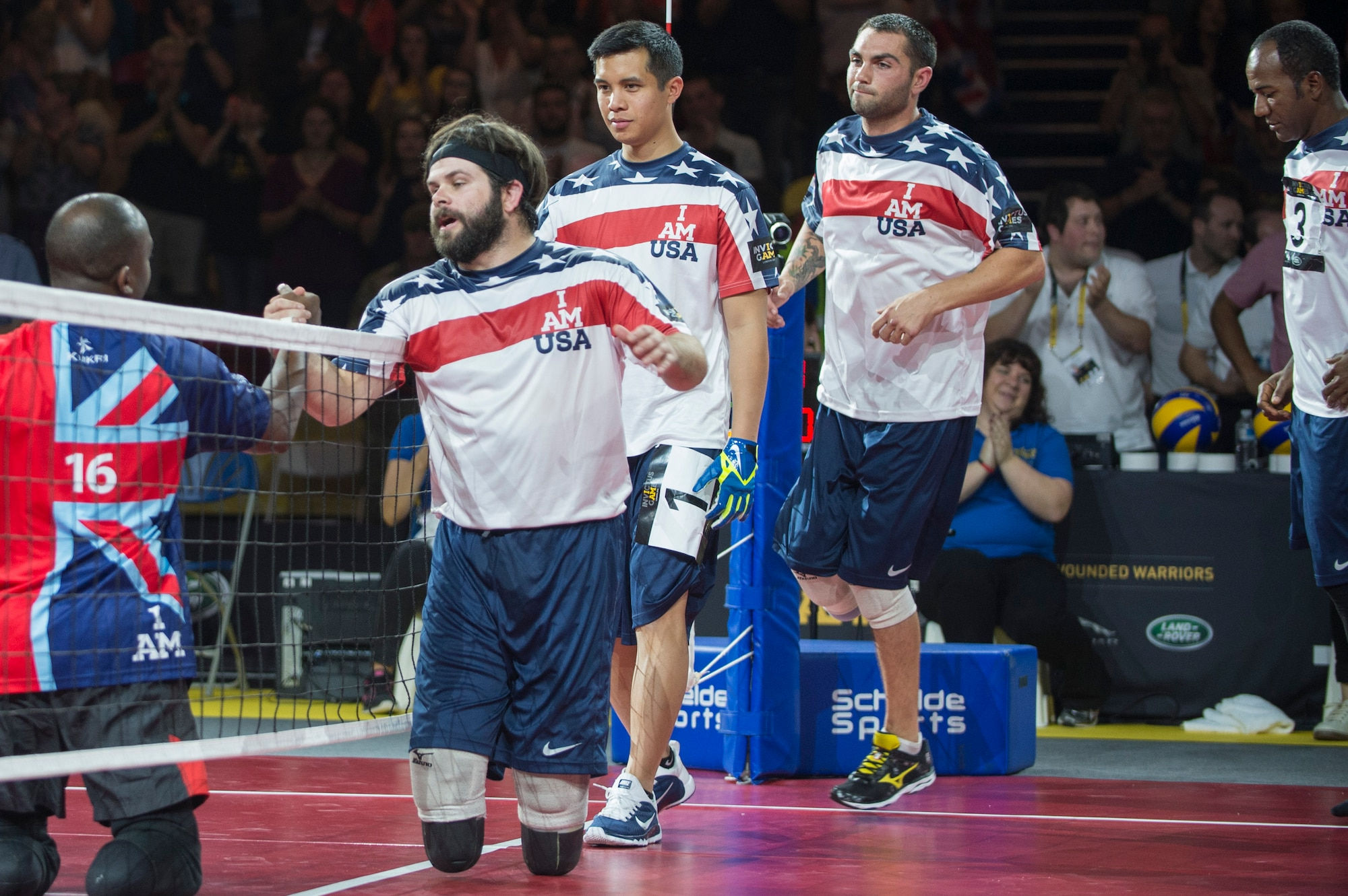 Navy Explosive Ordnance Disposal Technician 1st Class John Kremer and his U.S. teammates walk along the net to congratulate Great Britain, winners of the sitting volleyball event, at the inaugural Invictus Games Sept. 14, 2014, in London. Great Britain defeated the U.S. in a best-out-of-five match. The Invictus Games featured athletes competing in various Paralympic-style events, including swimming, track and field, seated volleyball, wheelchair basketball, and wheelchair rugby, among others. (U.S. Navy photo/Mass Communication Specialist 1st Class (SW) Mark Logico)