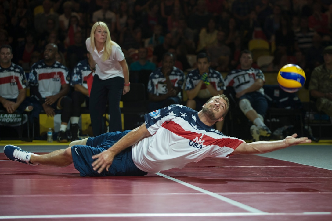 Navy Hospital Corpsman 2nd Class Max Rohn reaches for the ball during the sitting volleyball finals at the inaugural Invictus Games Sept. 14, 2014, in London. Great Britain defeated the U.S. in a best-out-of-five match. The Invictus Games featured athletes competing in various Paralympic-style events, including swimming, track and field, seated volleyball, wheelchair basketball, and wheelchair rugby, among others. (U.S. Navy photo/Mass Communication Specialist 1st Class (SW) Mark Logico)