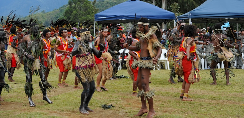 Staff Sgt. Melissa Pascua, Hawaii Air National Guard 154th Civil Engineer Squadron emergency management journeyman, center, performs a tribal dance with members of the Jiwaka Tribe during the closing ceremony for Pacific Unity 14-8. PACUNITY helps cultivate common bonds and fosters goodwill between the U.S. and regional nations through multi-lateral humanitarian assistance and civil military operations.  (U.S. Air Force photo by Tech. Sgt. Terri Paden/Released)
