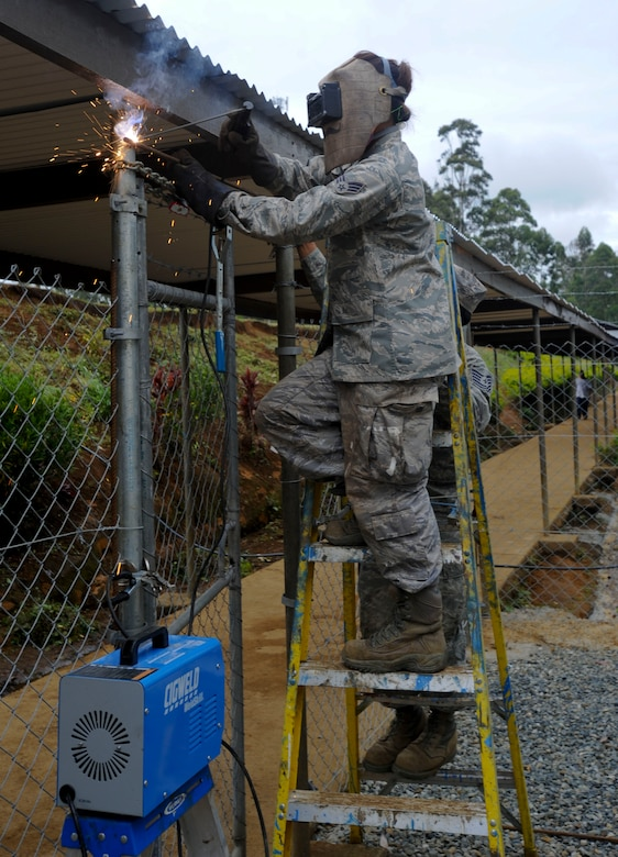 Senior Airman Jennie Abbott, Hawaii Air National Guard 154th Civil Engineer Squadron heavy equipment operator, welds rebar to a fence during Pacific Unity 14-8 in Mount Hagen, Papua New Guinea. As part of Pacific Unity the unit has been working on the construction of two new dormitories for female students, as well as performing other renovations and maintenance around the school. PACUNITY helps cultivate common bonds and fosters goodwill between the U.S. and regional nations through multi-lateral humanitarian assistance and civil military operations.  (U.S. Air Force photo by Tech. Sgt. Terri Paden/Released)