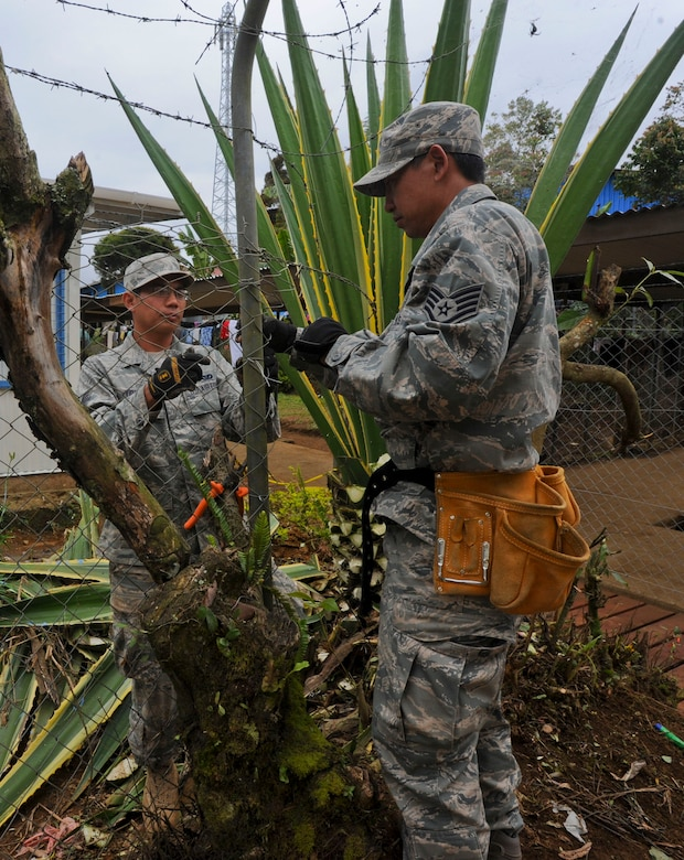 Senior Airman Paul Vidad, Hawaii Air National Guard 154th Civil Engineer Squadron engineering assistant, left, and Staff Sgt. Chris Aurio, Hawaii Air National Guard 154th Civil Engineer Squadron heating, ventilation and cooling journeyman, repair a fence at Togoba Secondary School in Mount Hagen, Papua New Guinea, as part of Pacific Unity 14-8. PACUNITY helps cultivate common bonds and fosters goodwill between the U.S. and regional nations through multi-lateral humanitarian assistance and civil military operations.  (U.S. Air Force photo by Tech. Sgt. Terri Paden/Released)