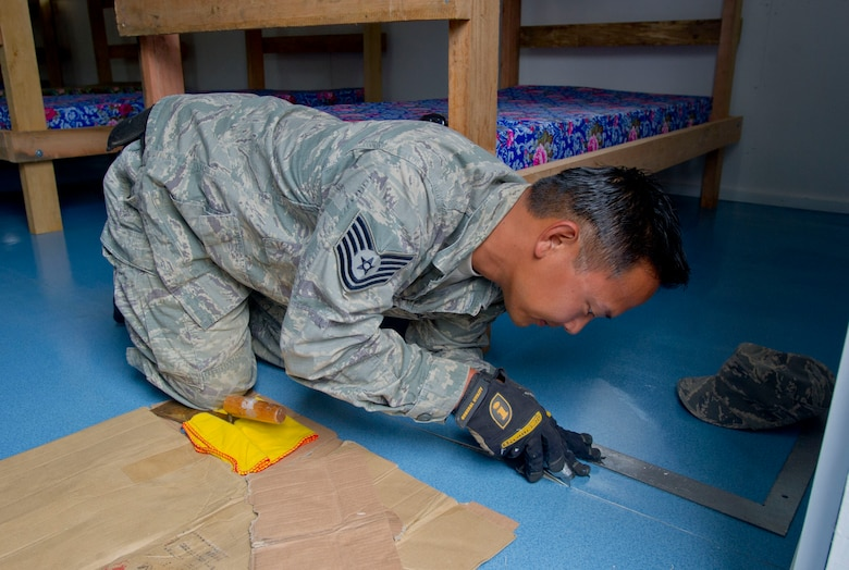 Tech. Sgt. Pat Takenishi, Hawaii Air National Guard 154th Civil Engineer Squadron heavy equipment operator works on the floor of a newly constructed dormitory at Togoba Secondary School in Mount Hagen Papua New Guinea, as part of Pacific Unity 14-8.  PACUNITY helps cultivate common bonds and fosters goodwill between the U.S. and regional nations through multi-lateral humanitarian assistance and civil military operations.  (U.S. Air Force photo by Tech. Sgt. Terri Paden/Released)