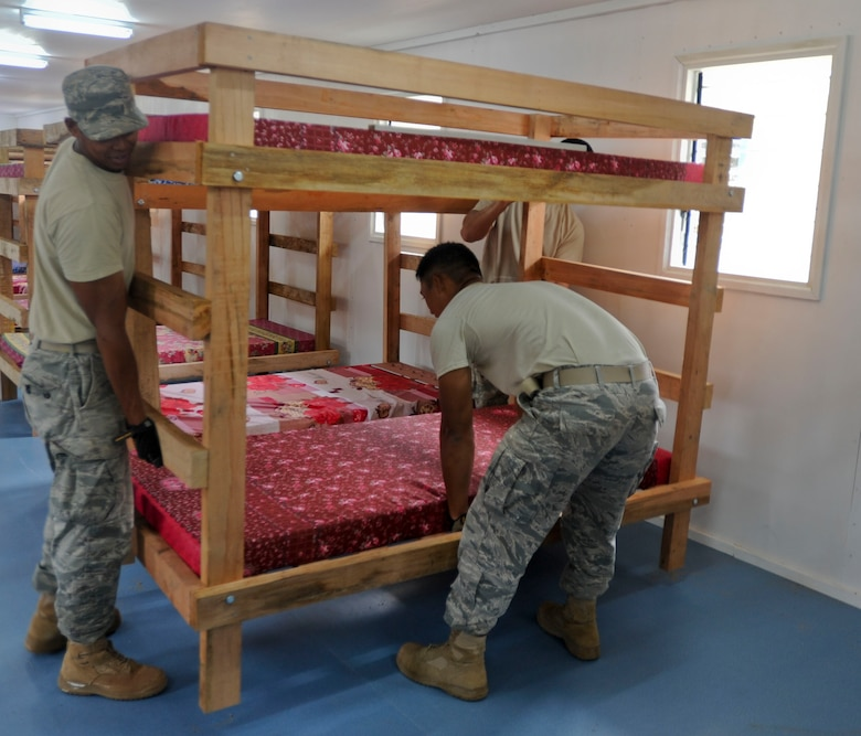 Members of the Hawaii Air National Guard 154th Civil Engineer Squadron move bunk beds into place inside a newly built dormitory at Togoba Secondary School as Pacific Unity 14-8 in Mount Hagen, Papua New Guinea, wraps up. PACUNITY helps cultivate common bonds and fosters goodwill between the U.S. and regional nations through multi-lateral humanitarian assistance and civil military operations.  (U.S. Air Force photo by Tech. Sgt. Terri Paden/Released)