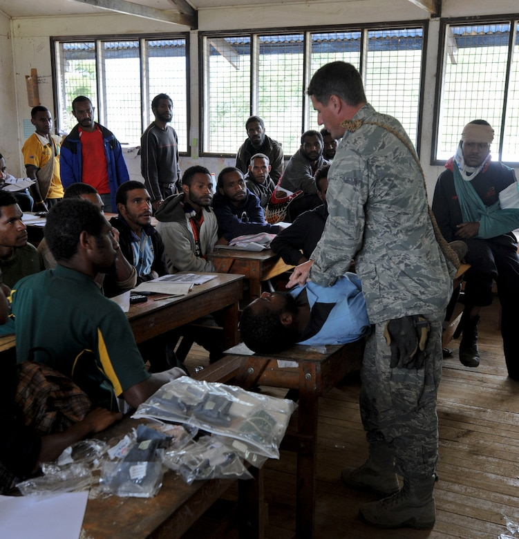 Maj. Nathaniel Duff, Hawaii Air National Guard 154th Medical Group and Pacific Unity 14-8 medical officer, demonstrates the proper way to wrap an injury during a basic first-aid clinic at Togoba Secondary School in Mount Hagen, Papua New Guinea. PACUNITY helps cultivate common bonds and fosters goodwill between the U.S. and regional nations through multi-lateral humanitarian assistance and civil military operations.  (U.S. Air Force photo by Tech. Sgt. Terri Paden/Released)