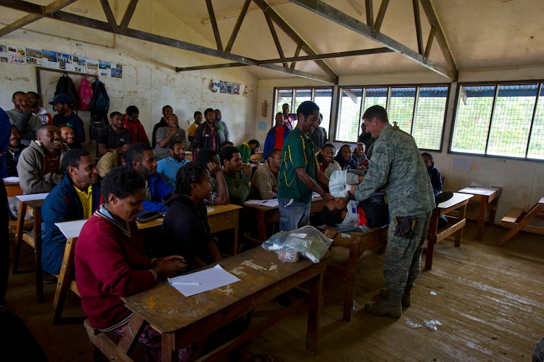 Maj. Nathaniel Duff, Hawaii Air National Guard 154th Medical Group and Pacific Unity 14-8 medical officer, shows a group of students how to perform cardiopulmonary resuscitation during a basic first-aid clinic at Togoba Secondary School in Mount Hagen, Papua New Guinea. PACUNITY helps cultivate common bonds and fosters goodwill between the U.S. and regional nations through multi-lateral humanitarian assistance and civil military operations.  (U.S. Air Force photo by Tech. Sgt. Terri Paden/Released)