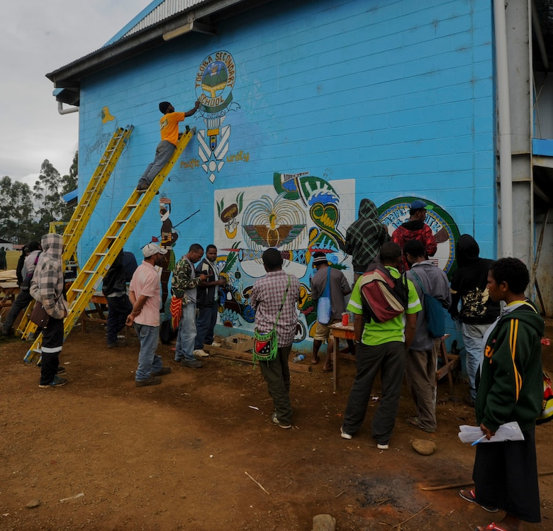 Students at Togoba Secondary School paint murals on the school walls in preparation for the Pacific Unity 14-8 closing ceremony in Mount Hagen, Papua New Guinea. PACUNITY helps cultivate common bonds and fosters goodwill between the U.S. and regional nations through multi-lateral humanitarian assistance and civil military operations.  (U.S. Air Force photo by Tech. Sgt. Terri Paden/Released)