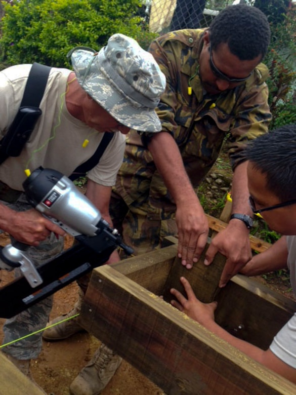Chief Master Sgt. Robert Davis, 154th Civil Engineer Squadron chief enlisted manager and structures subject matter expert, goes over construction plans with members of the Hawaii Air National Guard 154th Civil Engineer Squadron who have been working on the construction of two new dormitories at Togoba Secondary School in Mount Hagen, Papua New Guinea, as part of Pacific Unity 14-8. PACUNITY helps cultivate common bonds and fosters goodwill between the U.S. and regional nations through multi-lateral humanitarian assistance and civil military operations.  (U.S. Air Force photo by Airman 1st Class Jaimie Aquino/Released)
