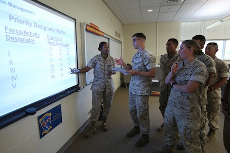 Staff Sergeant Sandra Fisher (far left), Instructor, Enlisted Supply Basic Course 15-14, Ground Supply School (GSS), Marine Corps Combat Service Support Schools, answers some of her Marine students questions for her class held aboard Camp Johnson, N.C. on June 3, 2014. (Combat Camera photo by Lance Corporal Laura Mercado/ Released)