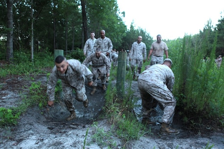 Marines with Ground Supply School (GSS), Marine Corps Combat Service Support Schools, move through mud and under constantine wire while moving through an endurance course aboard Camp Johnson, NC, June 23, 2014. Staff and student Marines of GSS participated in the team building event to build camaraderie, and cohesion within the schoolhouse. (U.S. Marine Corps Photo by Sergeant Mark E. Morrow) (Released)