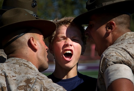 Sgts. Ryan Loya (left), Tyrone Evans (rear) and Jonathon Lopez (right), drill instructors from Marine Corps Recruit Depot San Diego, correct Levi Hopkins, a poolee from Recruiting Substation Everett, during Recruiting Station Seattle's annual west side pool function at Foster High School in Tukwila, Wash., Sept. 13, 2014. During the event, Washington-based recruiters teamed with drill instructors to physically and mentally prepare enlistees for boot camp. The enlistees, part of the Marine Corps delayed entry program, are awaiting their ship dates. Loya, 29, is from Bellevue, Wash. Evans, 25, is from Kokomo, Ind. Lopez, 28, is from San Juan, Puerto Rico. Hopkins, 17, is a senior at Lake Stevens High School and was recruited by Sgt. Jeff Otterson. (U.S. Marine Corps photo by Sgt. Reece Lodder)