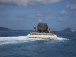 The LMCS, loaded with a Humvee, is towed to the beach near Mersing, Malaysia.