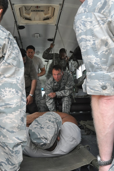 Lt. Col. Luke Lokowich, 5th Reconaissance Squadron commander, helps load a simulated patient into a medical bus while medical technicians observe the process, at Osan Air Base, Republic of Korea, Sept. 8, 2014.  Leadership from across Team Osan participated in the annual Mustang Immersion to develop a better understanding of what Osan Airmen are able to bring to the fight.  (U.S. Air Force photo/Capt. Robert Howard)