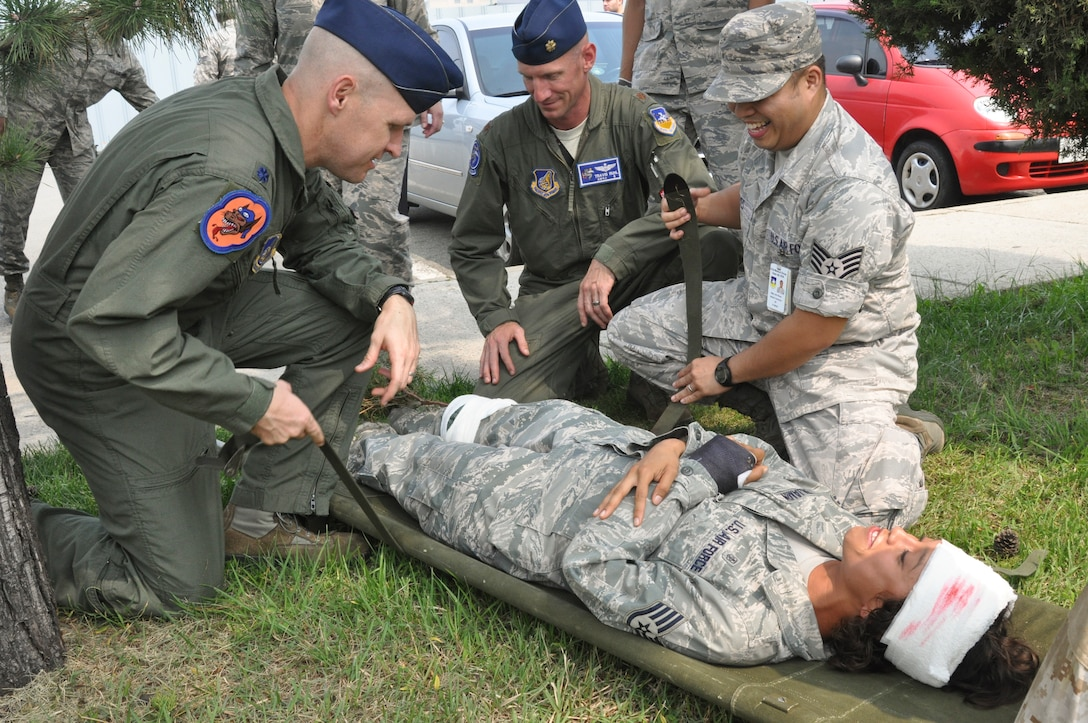 Lt. Col. Nicholas Evans, 36th Fighter Squadron commander, and Maj. Travis Ruhl, 51st Operations Support Squadron director of operations, attempt to secure a simulated patient with help from Staff Sgt. John Reyes, 51st Medical Group medical statistics technician, at Osan Air Base, Republic of Korea, Sept. 8, 2014.  Leadership from across Team Osan participated in the annual Mustang Immersion to develop a better understanding of what Osan Airmen are able to bring to the fight.  (U.S. Air Force photo/Capt. Robert Howard)