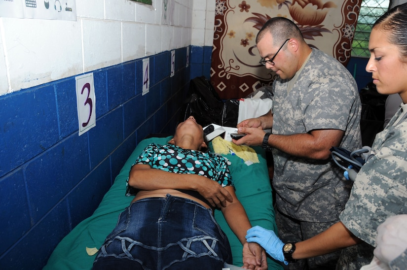 U.S. Army Sgts. Gary Aaron and Dionna Ferrell treat a woman who passed out due to an asthma attack and pneumonia. JTF-Bravo's Medical Element, in conjunction with the 1-228th Aviation Regiment, U.S. Embassy in San Salvador, the El Salvador Ministry of Health and El Salvador military, conducted a medical readiness training exercise (MEDRETE) in La Poza, Department of Usulután, El Salvador, September 8-11 where over 1,250 people received medical care. (Photo by U.S. Air National Guard Capt. Steven Stubbs)