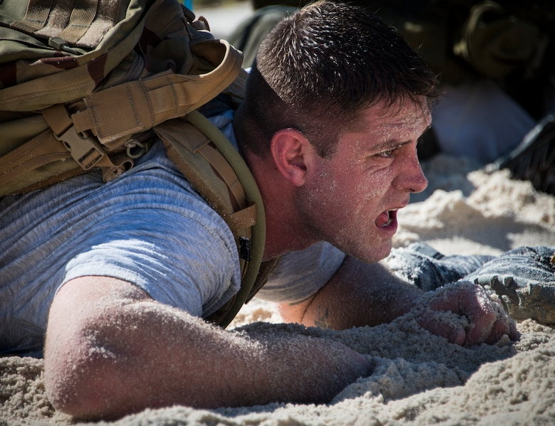 A participant low-crawls through the sand during the GORUCK Cohesion Challenge Sept. 11, at Eglin Air Force Base, Fla.  This elite team-building event, led by a Special Forces veteran, featured military inspired challenges and missions.  Only 24 out of the original 27 completed all obstacles.  Eglin is the fifth base to complete the Team Cohesion Challenge, which is modeled after special operations training.  (U.S. Air Force photo/Tech. Sgt. Jasmin Taylor)