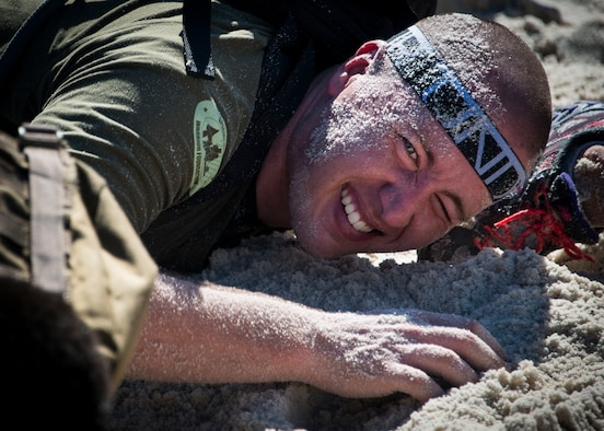 Thamas Church low crawls through the sand during the GORUCK Cohesion Challenge Sept. 11, at Eglin Air Force Base, Fla.  This elite team-building event, led by a Special Forces veteran, featured military inspired challenges and missions.  Only 24 out of the original 27 completed all obstacles.  Eglin is the fifth base to complete the Team Cohesion Challenge, which is modeled after special operations training.  (U.S. Air Force photo/Tech. Sgt. Jasmin Taylor)