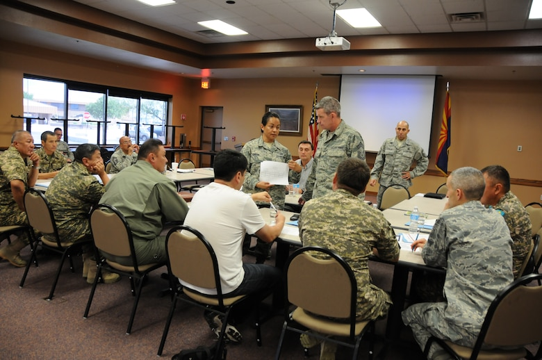 Chief Master Sgt. Martha Garcia, 161st Air Refueling Wing command chief, explains an Air Force organizational chart during an NCO information exchange Sept. 9, 2014. The Arizona Air National Guard welcomed seven members of the Kazakhstan military Sept. 8 through 12, 2014, as part of the National Guard's State Partnership Program. The program is designed as an information exchange with the purpose of fostering mutual interests and long-term relationships. (U.S. Air National Guard photo by 2nd Lt. Susan Gladstein/Released)