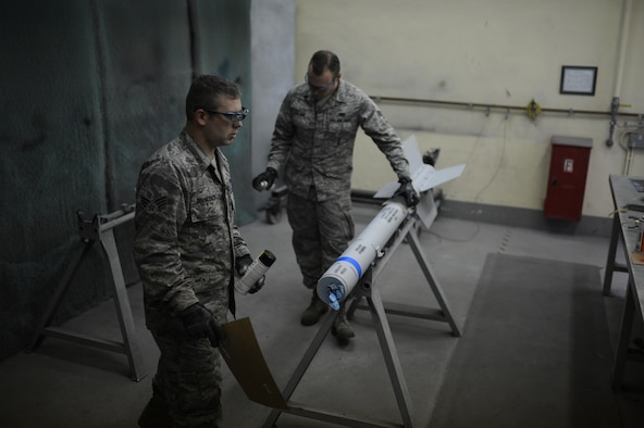 U.S. Air Force Senior Airmen Daniel Devincenzo and Senior Airman Anthony Valliere, 52nd Equipment Maintenance Squadron precision guided munitions technicians and natives of Parsippany, N.J., and Chandler, Ariz. respectively, apply the finishing markings on an AIM-9 sidewinder missile on Spangdahlem Air Base, Germany, Sept. 10, 2014. Airmen use training rounds, which are hollow shells with no electronic components and marked with blue rings, to practice real-world operations without handling or damaging live munitions. (U.S. Air Force photo by Senior Airman Gustavo Castillo/Released)