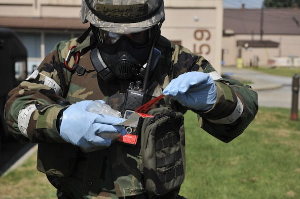 Master Sgt. Thomas Longworth, 51st Civil Engineering Squadron commander inspection program manager, peels off lab sample tape to place on a container holding simulated biological chemicals during a simulated biological response training event on Osan Air Base, ROK, Sept. 16, 2014. The U.S. Airmen demonstrated how they deploy to a scene, pull a sample and transport it to a laboratory for further analysis. (U.S. Air Force photo by Senior Airman David Owsianka)