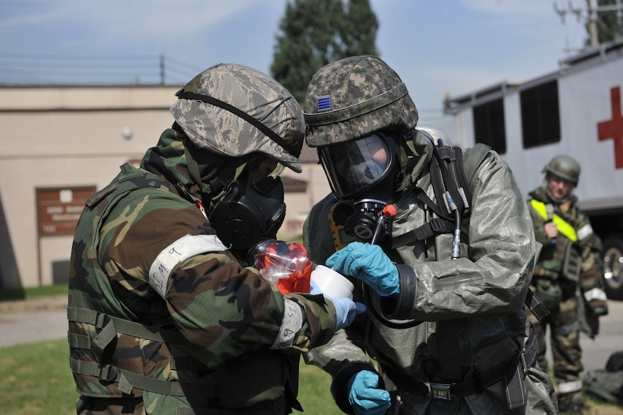 Senior Airman Eva Gaus, 51st Civil Engineering Squadron readiness and emergency management flight journeyman, left, talks as Republic of Korea air force Senior Airman Woo Yong Chang, ROKAF decontamination team member, translates the information in Korean during a simulated biological response training event on Osan Air Base, ROK, Sept. 16, 2014. Both services worked together to improve each their mission capability. (U.S. Air Force photo by Senior Airman David Owsianka))