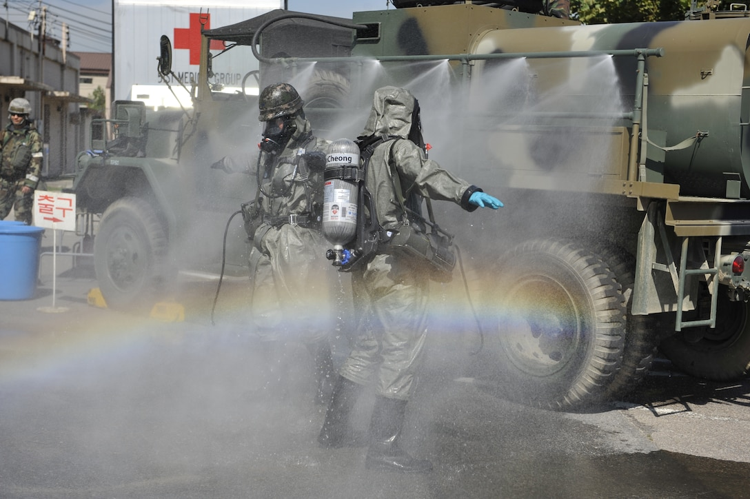 Members of the Republic of Korea air force wash off at a decontamination site after checking for biological samples in a contaminated area during a simulated biological response training event on Osan Air Base, ROK, Sept. 16, 2014. The ROKAF and U.S. Air Force worked together to improve their mission capability. (U.S. Air Force photo by Senior Airman David Owsianka)