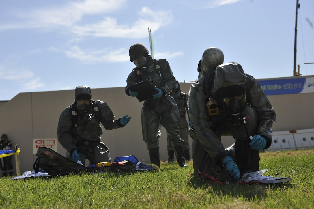 Members of the Republic of Korea air force set up their gear to sample a simulated biological chemical during a simulated biological response training event on Osan Air Base, ROK, Sept. 16, 2014. The ROKAF airmen demonstrated their capabilities by pulling a sample, decontaminating the area and then decontaminating the personnel. (U.S. Air Force photo by Senior Airman David Owsianka)