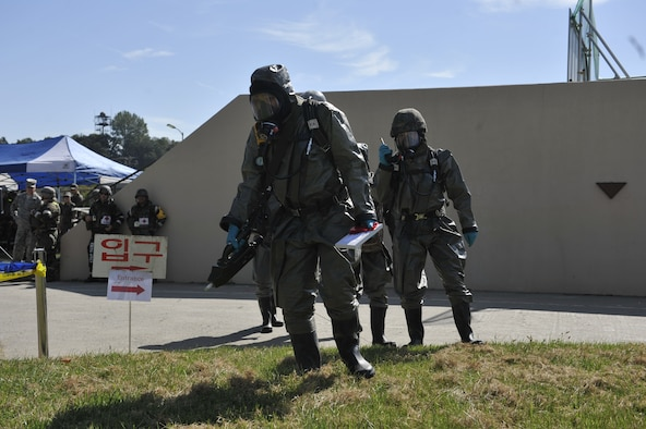 Members of the Republic of Korea air force walk onto a simulated contaminated area during a simulated biological response training event on Osan Air Base, ROK, Sept. 16, 2014. The ROKAF airmen demonstrated their capabilities by pulling a sample, decontaminating the area and then decontaminating the personnel. (U.S. Air Force photo by Senior Airman David Owsianka)