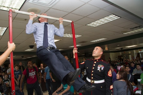 Matthew M. Lesar, the principal of Nathan Hale High School, knocks out a total of fourteen pull-ups during the Great American Rivalry Series between Nathan Hale and West Allis Central High School, Sept. 17, 2014.  Each school will take on the Chin-Up Challenge in the days leading up to the Great American Rivalry game on Friday, Sept. 19.  Nathan Hale High School completed 1,522 pull-ups and will have a chance to add to that total on game day.