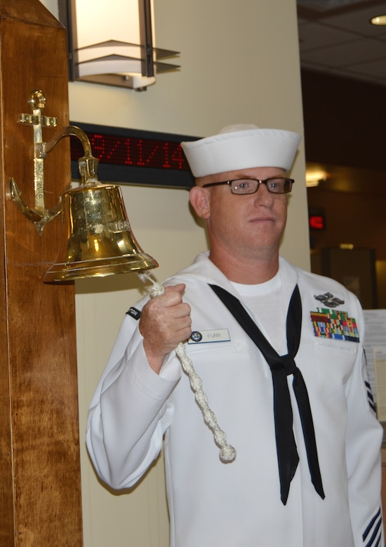 Petty Officer 1st Class John Furr, Naval Health Clinic Charleston hospital corpsman, rings a bell three times in the NHCC atrium, Sept. 11, 2014, at NHCC on Joint Base Charleston, S.C. Each ring of the bell represented one of the sites terrorists attacked on 9/11 - the World Trade Center, the Pentagon and Shanksville, Pa. (U.S. Navy photo/Petty Officer 3rd Class Caralyn Mulyk)