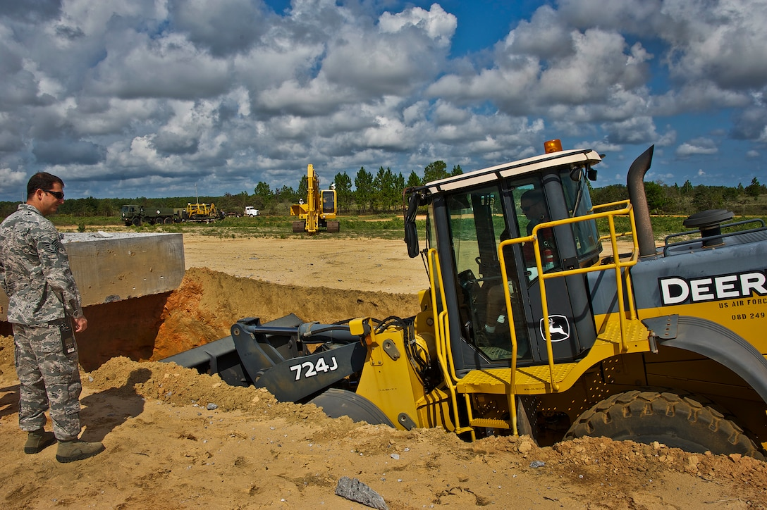 Tech. Sgt. James Fitzgerald, 96th Civil Engineer Squadron explosive ordnance disposal robotics section team lead, monitors the progress of the Eglin range services personnel preparing a path for a remotely controlled robot Sept. 9. His team responded to the call of robot services needed on Eglin's range to retrieve a test item for the 96th Test Wing's fuze program. The unique Air Force capability of remotely digging a site for ordnance retrieval is something only Eglin's EOD robotics team can do. (U.S. Air Force photo/Chrissy Cuttita)