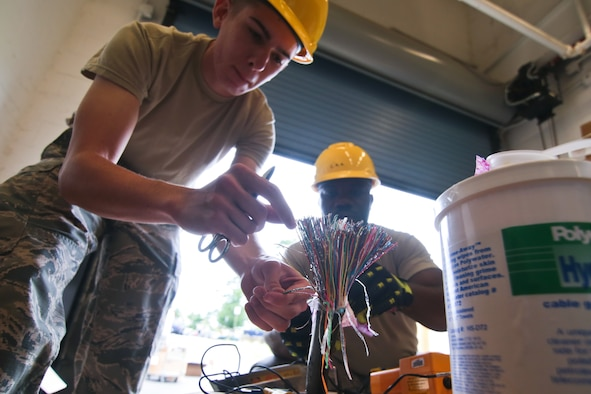 A picture of U.S. Air Force Airman 1st Class Jonathan Tuxbury and Senior Airman Charles Agyemang, both from the 212th Engineering Installation Squadron, preparing wiring for a job.