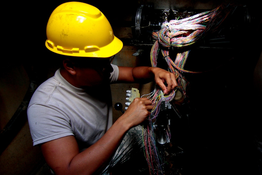 An Airman from the Massachusetts Air National Guard's 212th Engineering Installation Squadron splices wires in a manhole at Atlantic City Air National Guard Base, N.J., Sept. 16, 2014. The 212th EIS is assisting the 177th Fighter Wing with a communications infrastructure upgrade. (U.S. Air National Guard photo by Tech. Sgt. Matt Hecht/Released)
