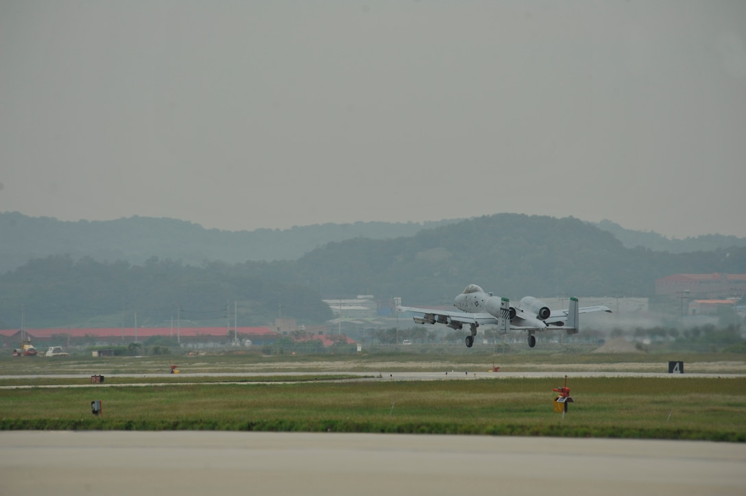 An A-10 Thunderbolt II from the 25th Fighter Squadron takes off from the runway in a mass launch during the operational readiness exercise Beverly Midnight 14-4 Sept. 17, 2014, at Osan Air Base, Republic of Korea. A total of 38 jets were launched during the mass launch. (U.S. Air Force photo by Senior Airman David Owsianka)