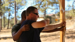 Lance Cpl. Carlos Morris, admin specialist, Headquarters Battalion, helps camper, Chase Neiberger learn how to shoot an archery bow at Camp Ronald McDonald in Mountain Center, Calif. on Sept. 13, 2014. Desert Arc has provided disabled adults with care and life skills for approximately 55 years.