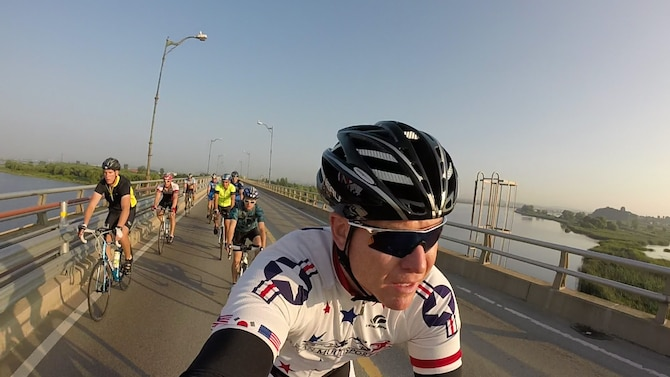Bill Goins, 8th Medical Operations Support health promotion program coordinator, bikes over a bridge as part of a nine-person team during a 125-mile bike ride from Osan Air Base, Republic of Korea, to Kunsan AB, Aug. 30, 2014. Goins and Wolf Pack Airmen have been making the annual trek for seven years. (Courtesy photo by Bill Goins)
