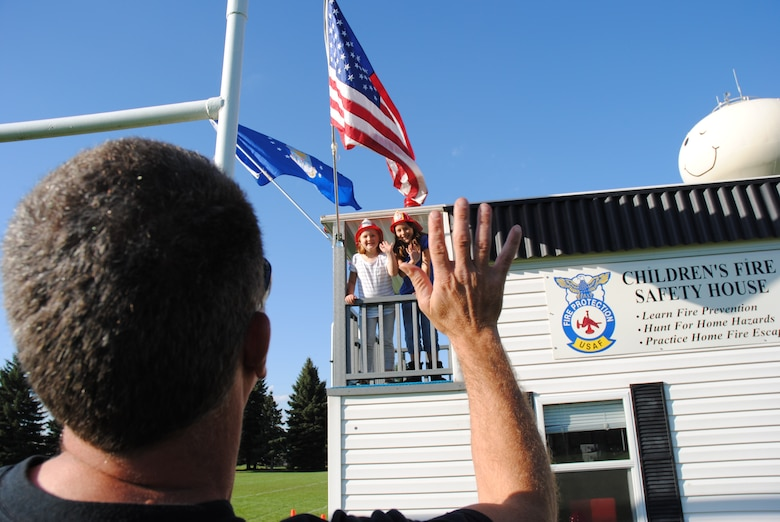 Grand Forks residents, Izzy and Zoe Cwikla wave to their father, Dan, from the small balcony of the Kids Fire Safety House during the Grand Cities Community Celebration, Sept. 15, 2014, on the grounds of the Cliff Fido Purpur Arena in downtown Grand Forks, N.D. The Kids Fire Safety House is used by the Grand Forks Air Force Base Fire Department to teach children fire prevention skills by hunting for home fire hazards and practicing fire escape drills.  (U.S. Air Force photo/Staff Sgt. Luis Loza Gutierrez)