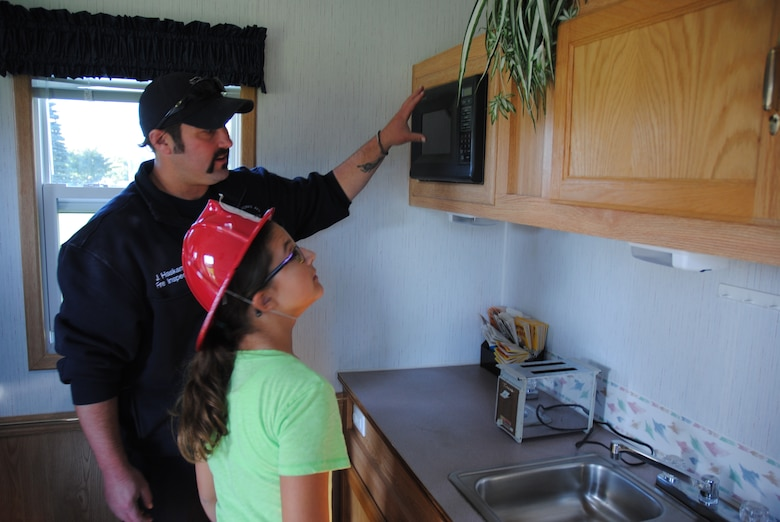 Air Force civilian fireman Justin Haskamp asks a young guest to identify as many fire hazards inside the small kitchen of the Kids Fire Safety House during the Grand Cities Community Celebration, Sept. 15, 2014, on the grounds of the Cliff Fido Purpur Arena in downtown Grand Forks, N.D. The Kids Fire Safety House is used by the Grand Forks Air Force Base Fire Department to teach children fire prevention skills by hunting for home fire hazards and practicing fire escape drills.  (U.S. Air Force photo/Staff Sgt. Luis Loza Gutierrez)