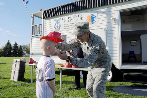 Staff Sgt. Stephen Hjersted helps a young guest properly put on a plastic Grand Forks AFB Grand Forks Junior Firefighters helmet during the Grand Cities Community Celebration, Sept. 15, 2014, on the grounds of the Cliff Fido Purpur Arena in downtown Grand Forks, North Dakota. Hjersted was one of four members from the base fire department who enjoyed meeting, greeting and educating guests on how to keep their communities safe by learning about fire prevention. (U.S. Air Force photo/Staff Sgt. Luis Loza Gutierrez)