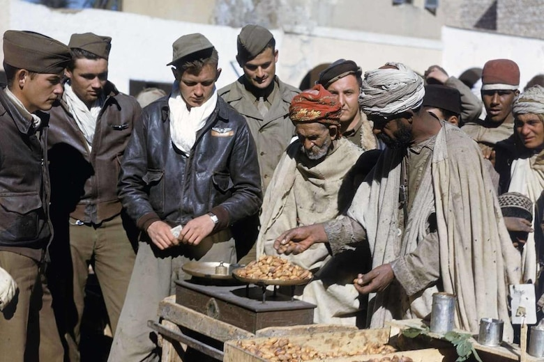 In December 1943/January 1944, several 12th Air Force enlisted aircrew members barter with local Arabs for dates while stationed in Algeria. (Courtesy Photo)