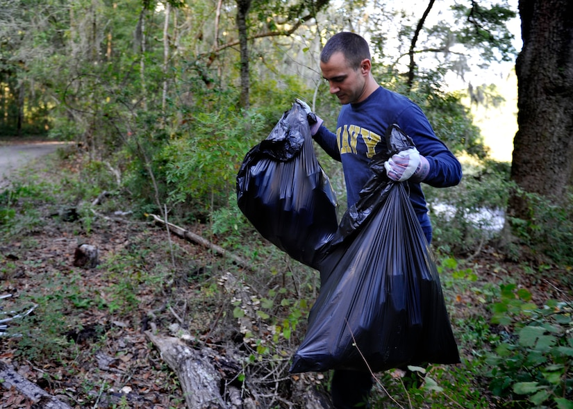Chief Petty Officer Selectee Jon Everett, Naval Nuclear Power Training Command, collects debris from the Peas Hill Creek during a chief petty officer selectee community project Sept. 13, 2014, near James Island, S.C. Chief selectees participate in COMREL projects as part of the CPO 365 Phase 2 training. The project was coordinated with Keep Charleston Beautiful, an organization that encourages local groups to volunteer for clean-up projects across the state by providing trash bags, gloves and any necessary supplies they might need. The chief selectees pinned on their anchors Sept. 16. (U.S. Air Force photo/Staff Sgt. Renae Pittman)